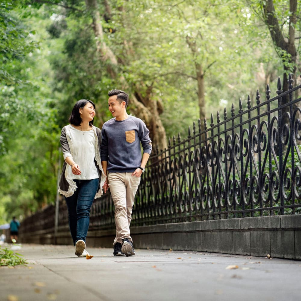 Couple going for a stroll on the tree-lined pathway at a park near Oaks Hackberry Creek in Irving, Texas