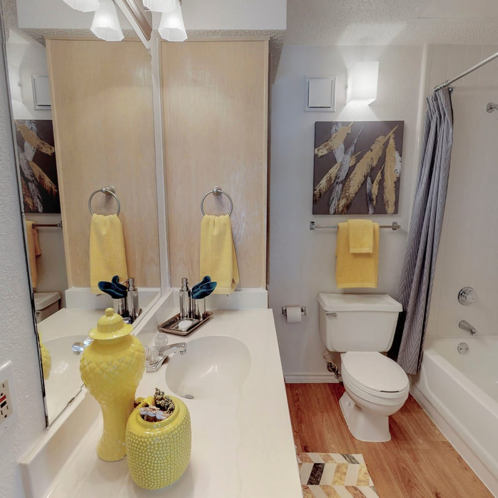 Large vanity mirror and wood-style flooring in a model apartment's bathroom at Oaks Hackberry Creek in Irving, Texas