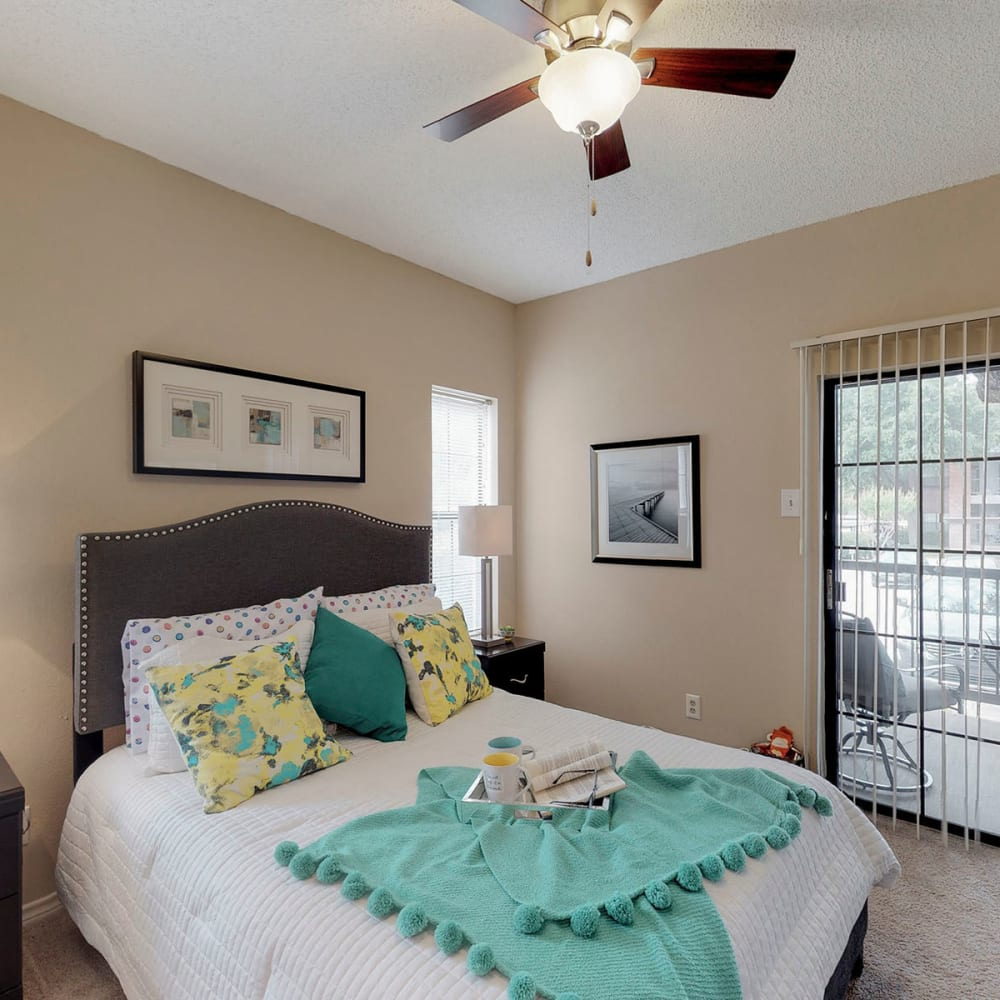 Model apartment's primary bedroom with plush carpeting and a ceiling fan at Oaks Hackberry Creek in Irving, Texas