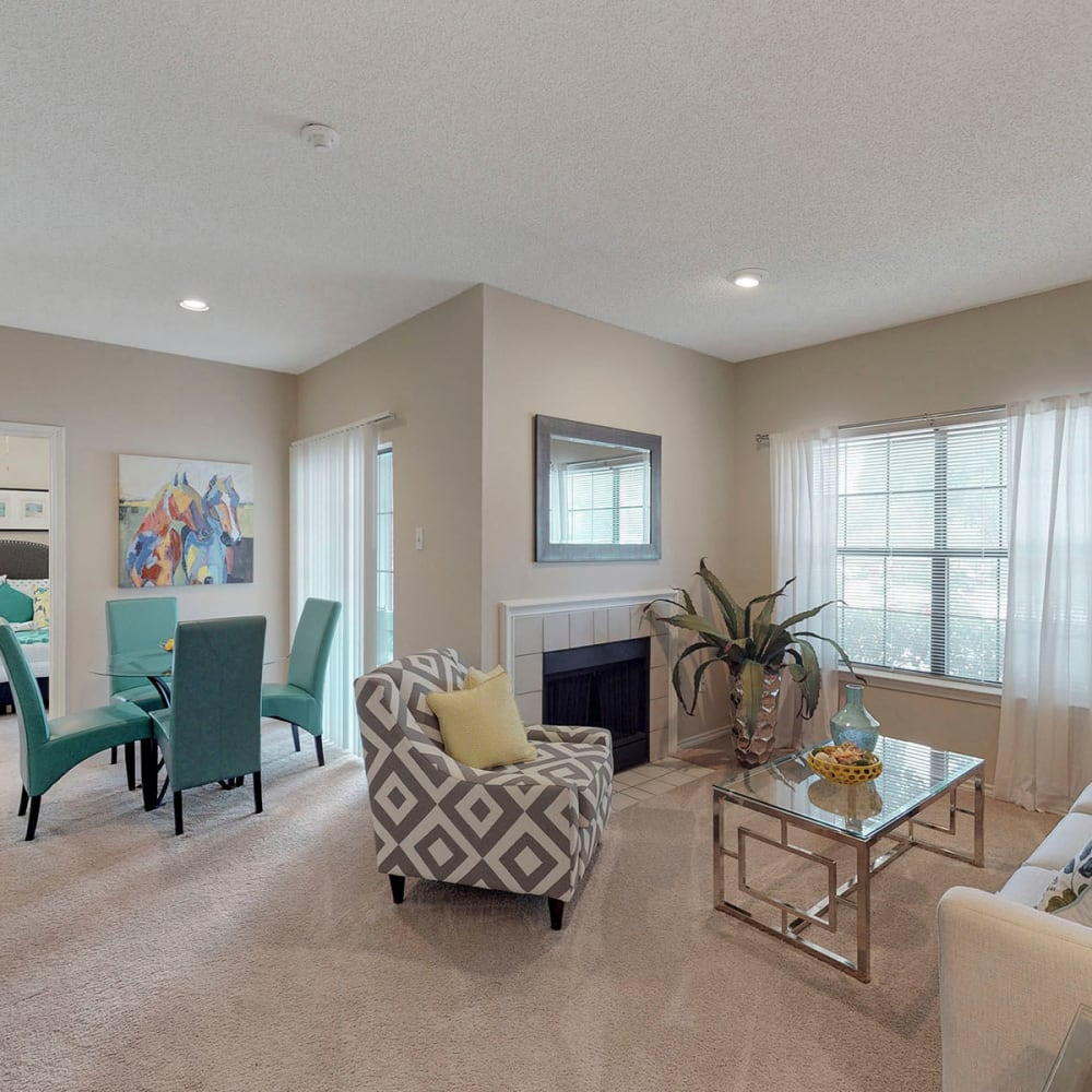 Plush carpeting and modern furnishings in the open-concept living area of a model apartment at Oaks Hackberry Creek in Las Colinas, Texas