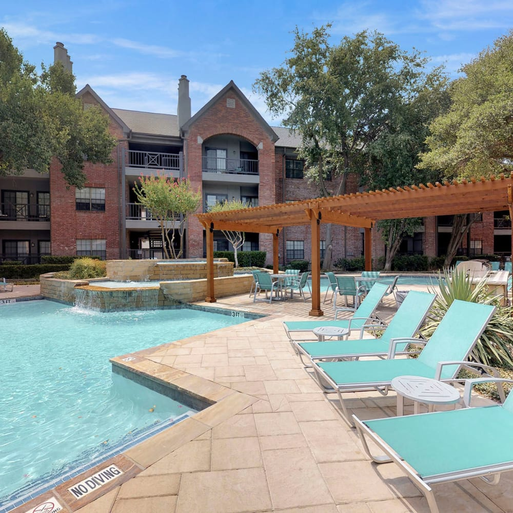 Pergola near chaise lounge chairs by the pool at Oaks Hackberry Creek in Las Colinas, Texas