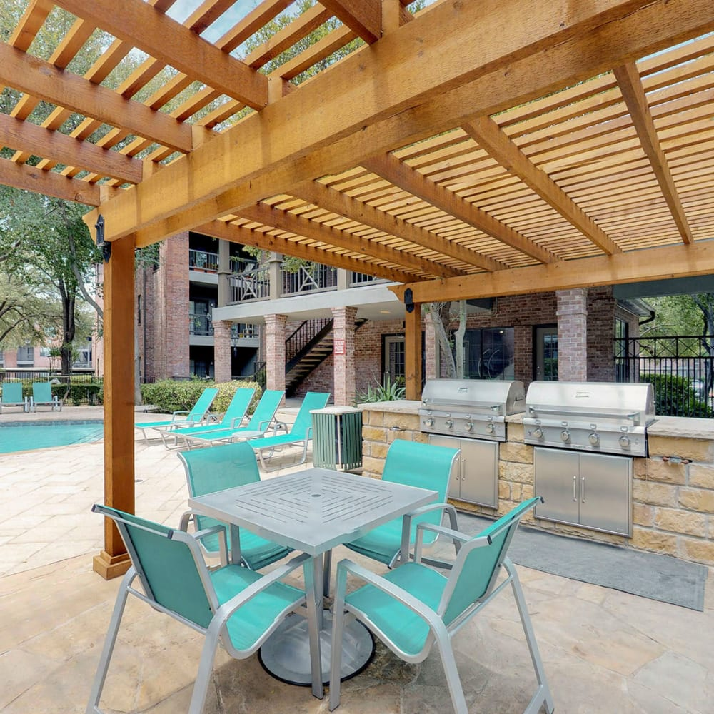 Pergola providing partial shade over a table and chairs near the barbecue area at Oaks Hackberry Creek in Las Colinas, Texas