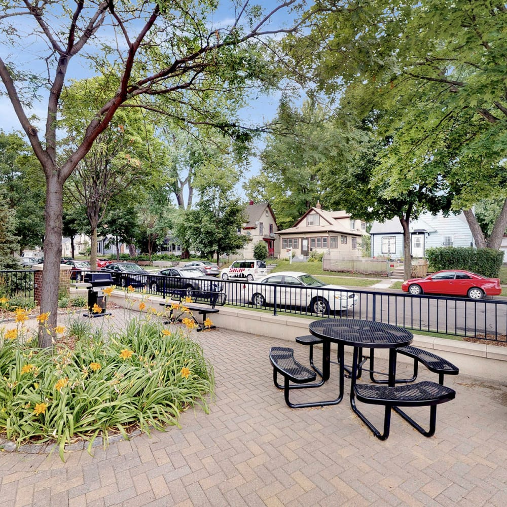 Picnic table in a courtyard surrounded by mature trees at Oaks Hiawatha Station in Minneapolis, Minnesota