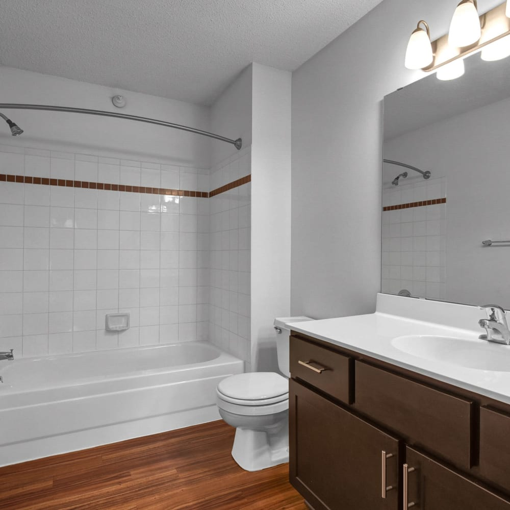 Tiled shower and hardwood flooring in a model townhome's bathroom at Oaks Lincoln Apartments & Townhomes in Edina, Minnesota