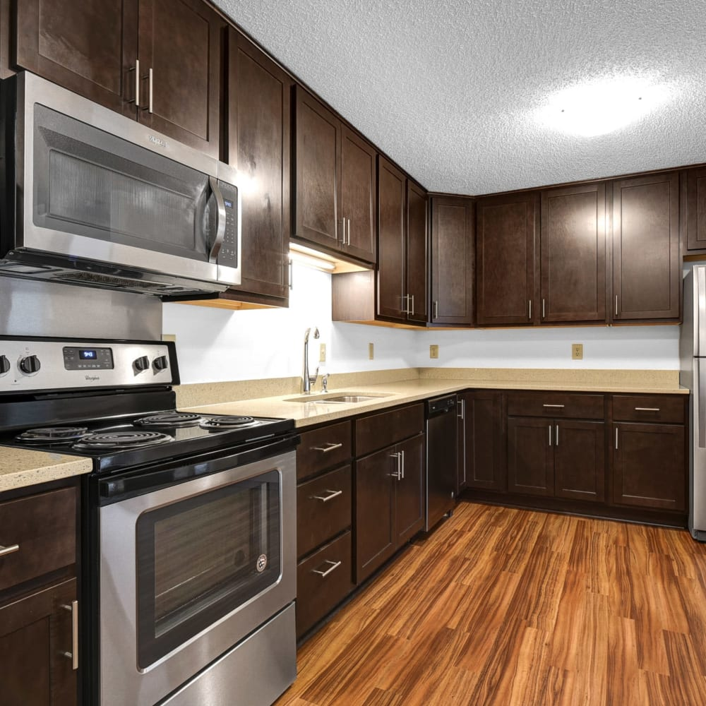 Hardwood flooring and dark wood cabinetry in a model townhome's kitchen at Oaks Lincoln Apartments & Townhomes in Edina, Minnesota