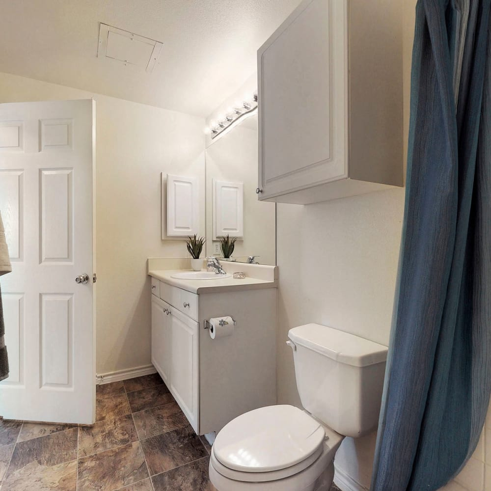 Extra storage cabinet and slate tile flooring in a model home's bathroom at Oaks Riverchase in Coppell, Texas
