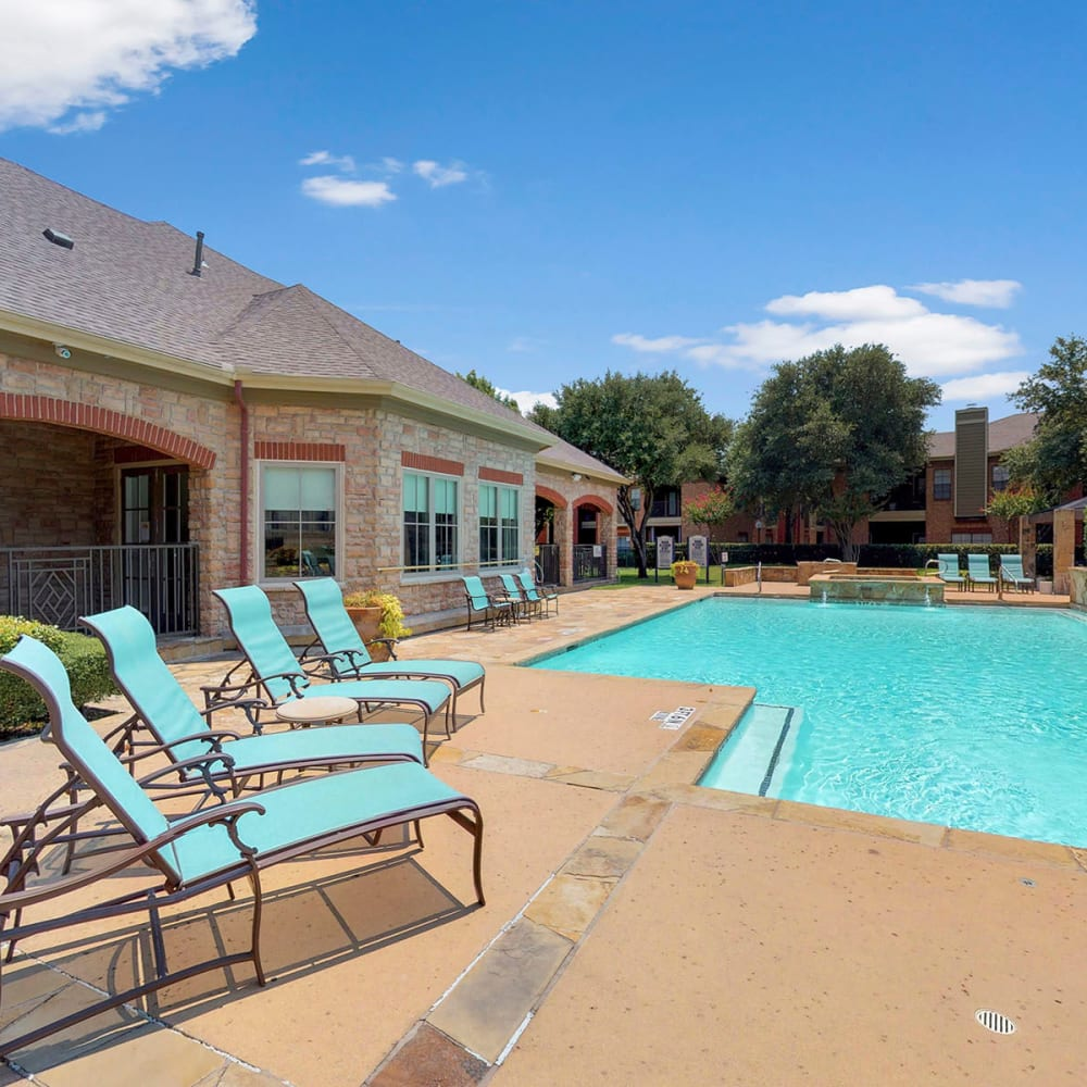 Lounge chairs on the sun deck near the pool at Oaks Riverchase in Coppell, Texas