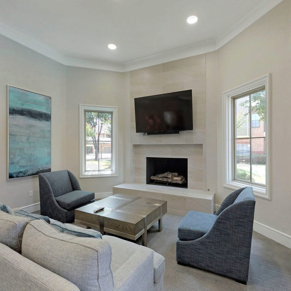 Lounge area with a flatscreen TV and a fireplace in the resident clubhouse at Oaks Riverchase in Coppell, Texas