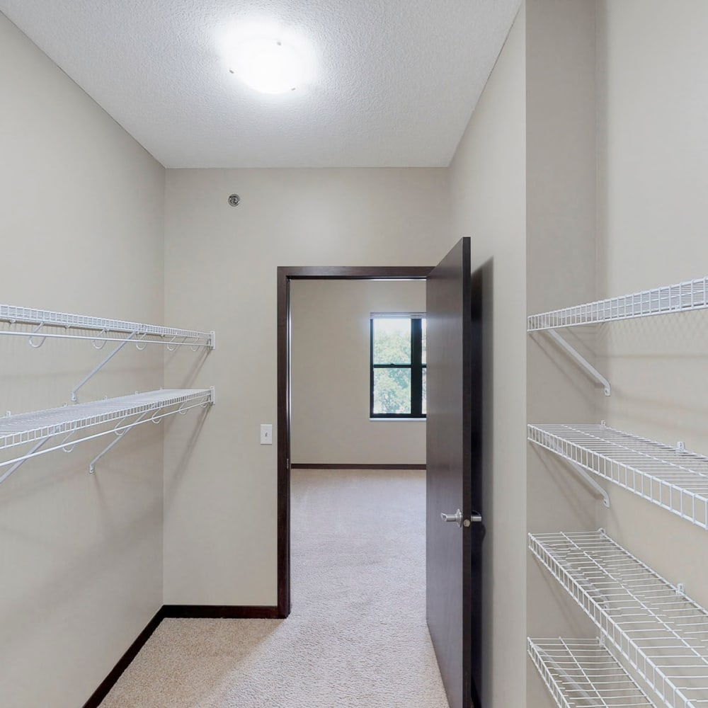 Large walk-in closet with ample shelving in a model home's primary bedroom at Oaks Station Place in Minneapolis, Minnesota