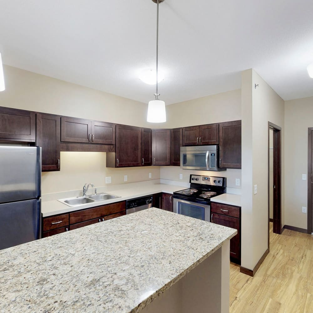 Spacious chef-inspired kitchen with an island and espresso wood cabinetry in a model apartment at Oaks Station Place in Minneapolis, Minnesota