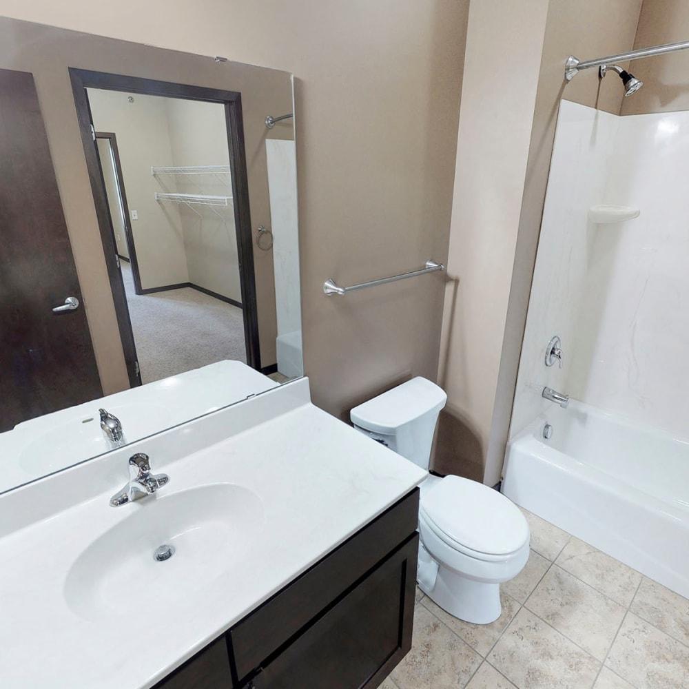Large vanity mirror in a model apartment's main bedroom's en suite bathroom at Oaks Station Place in Minneapolis, Minnesota