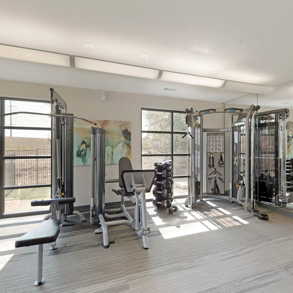 Free weights and exercise equipment in the onsite fitness center at Oaks Trinity in Dallas, Texas