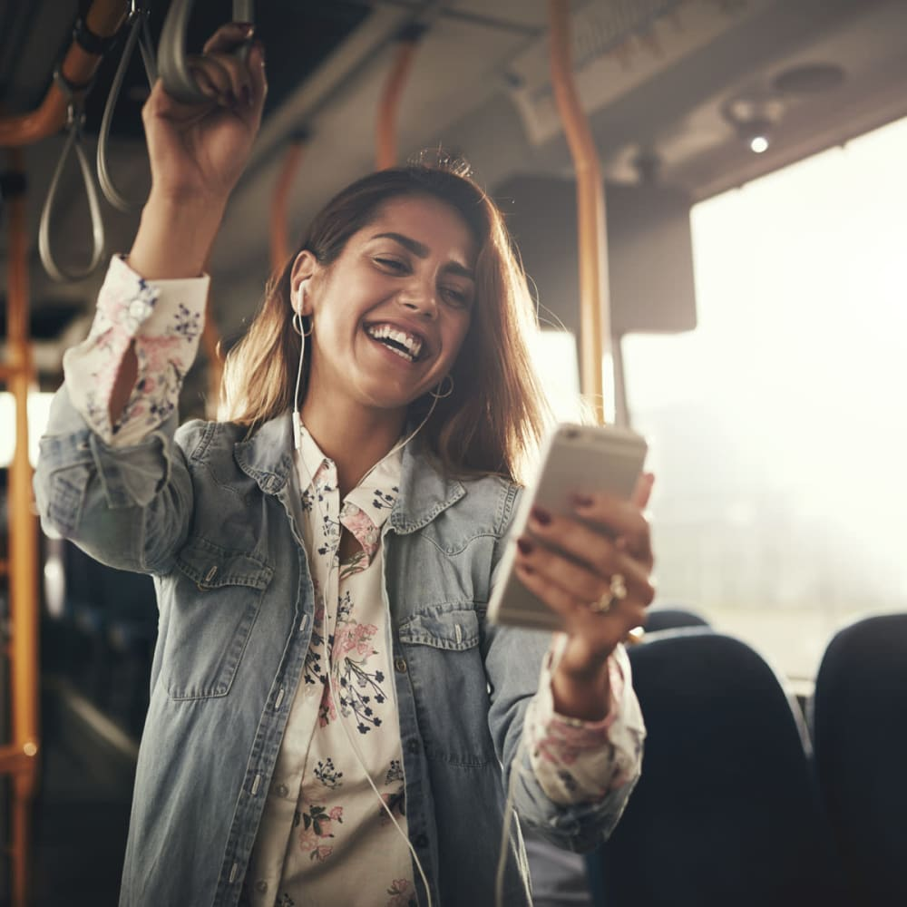Resident laughing at something on her smartphone while riding the bus to work near Oaks Union Depot in St. Paul, Minnesota