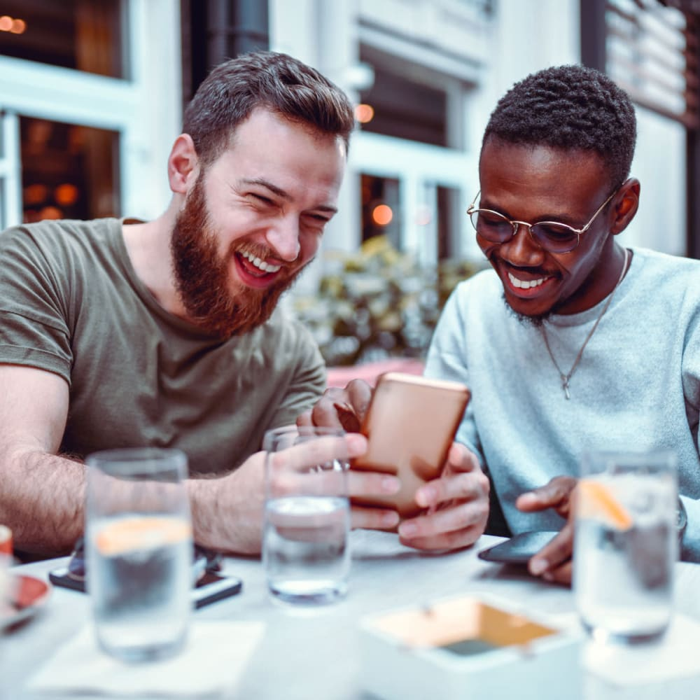 Resident couple laughing at something on their smartphones while seated outside at a downtown restaurant near Oaks White Rock in Dallas, Texas