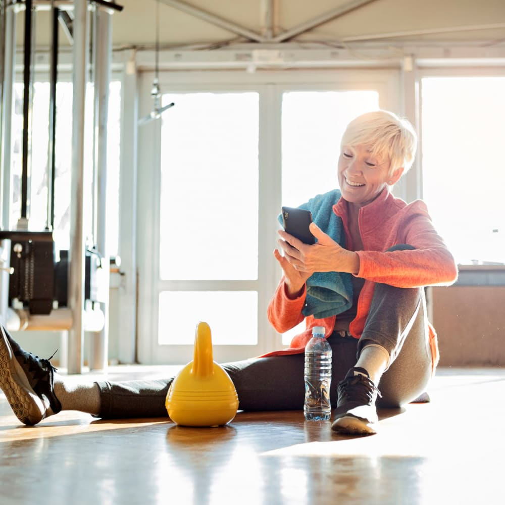 Resident taking a break between sets in the fitness center at Oaks White Rock in Dallas, Texas