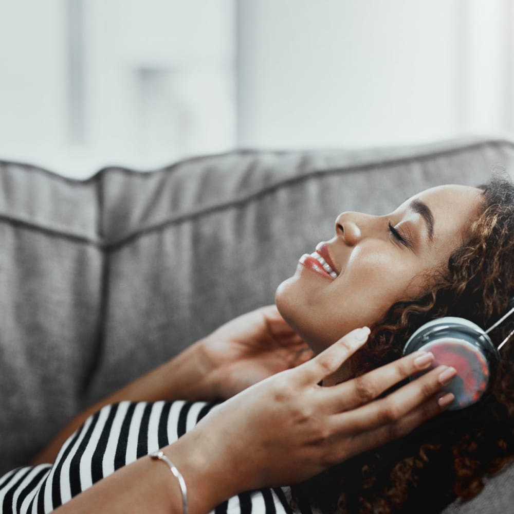 Resident relaxing on the couch and enthralled by the music on her headphones in her home at Oaks White Rock in Dallas, Texas