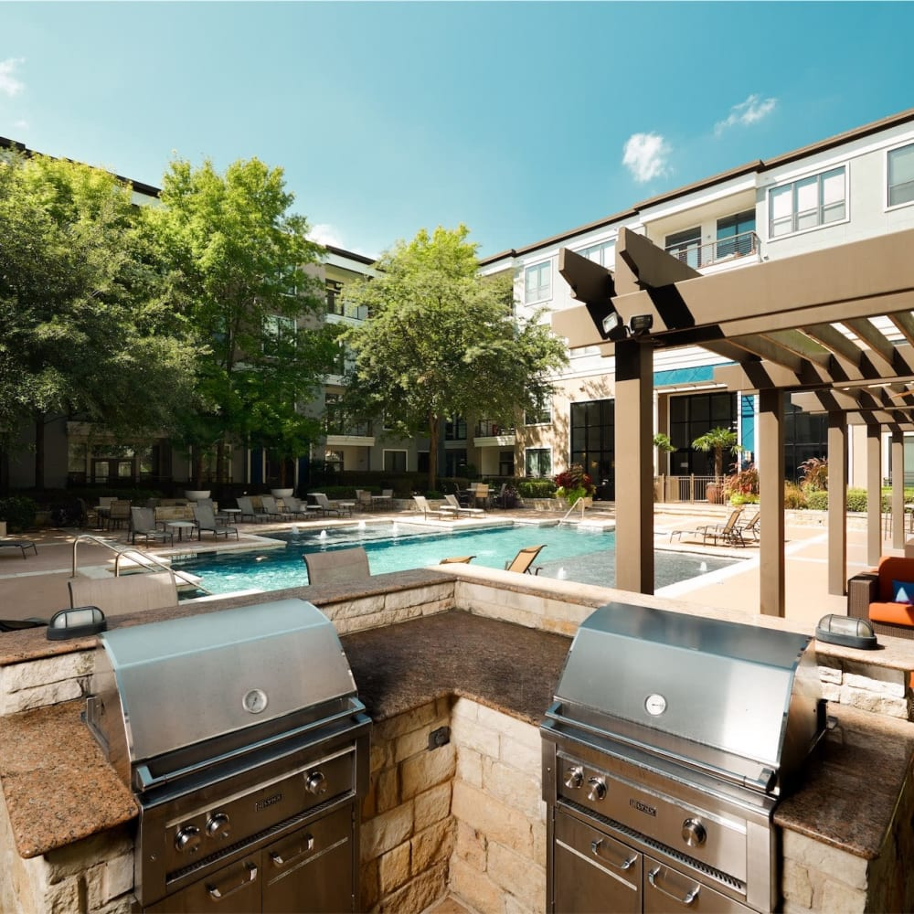 Bbq area next to pool with dual grills and lots of places to sit and eat at Seville Uptown in Dallas, Texas