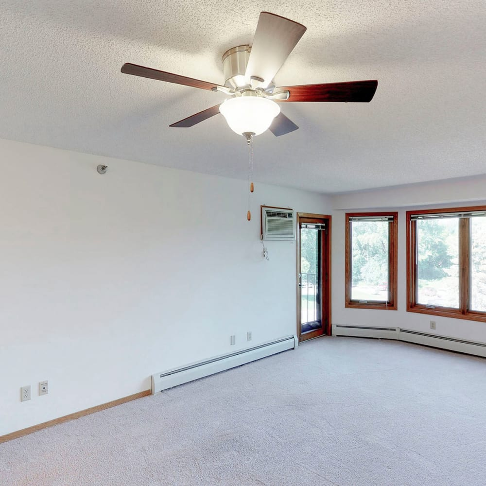 Spacious living area with a ceiling fan and plush carpeting in a townhome at Oaks Lincoln Apartments & Townhomes in Edina, Minnesota