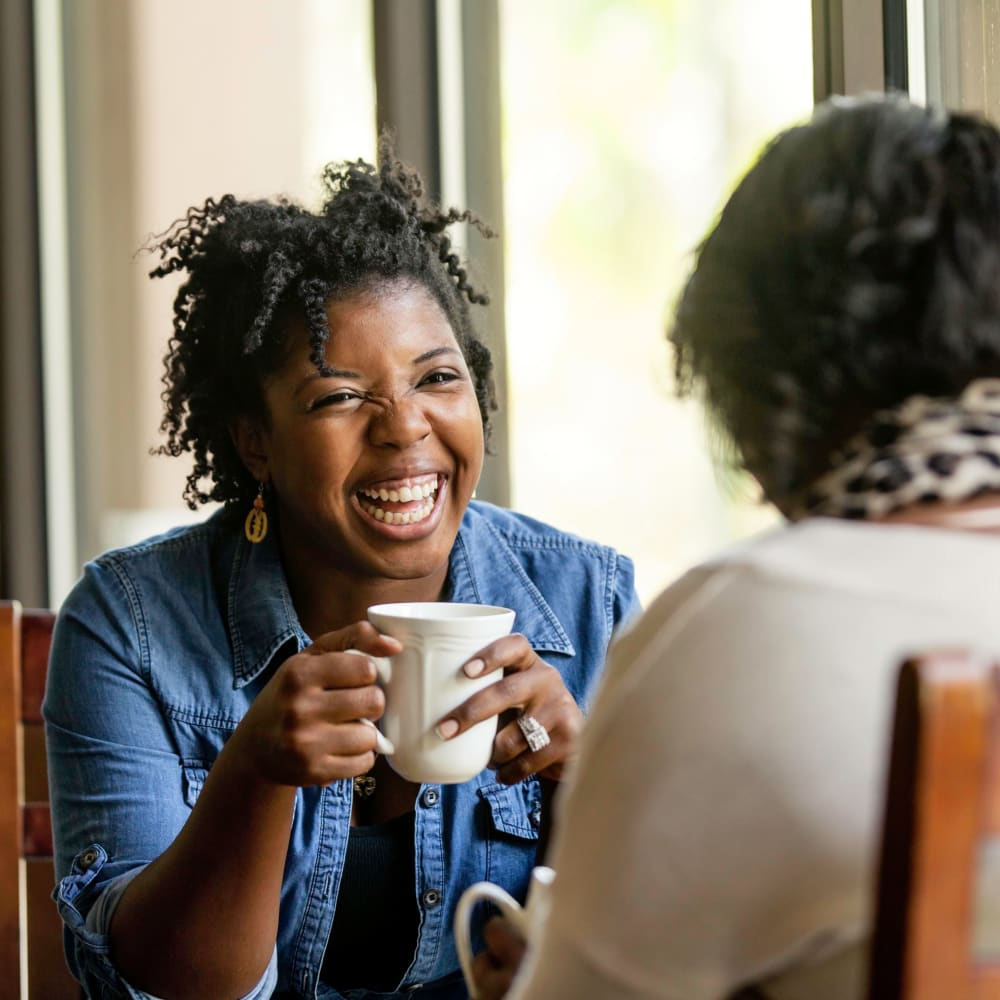 Friends laughing together over a cup of coffee near Vidorra McKinney Avenue in Dallas, Texas