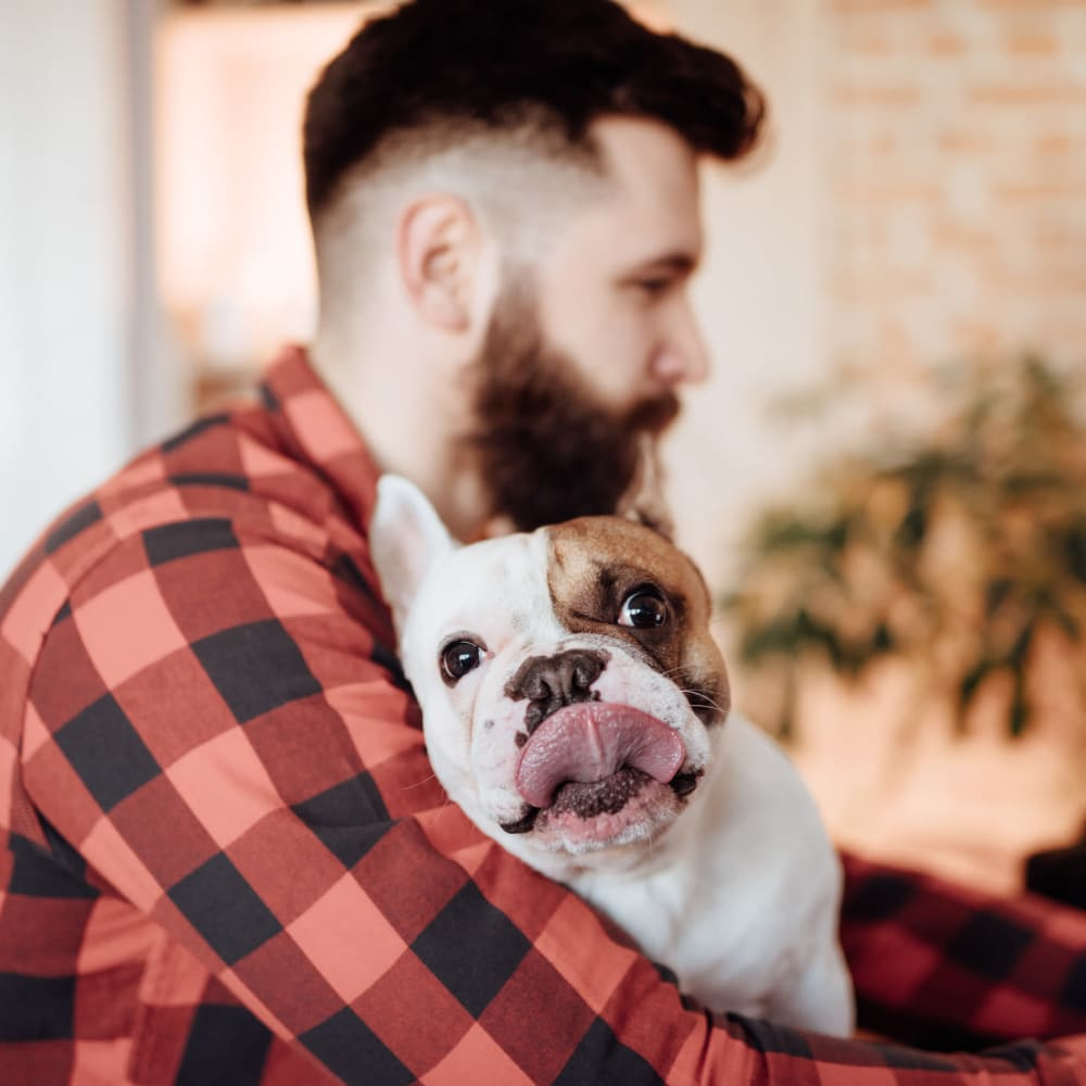 Resident hugging his dog at Newnan Lofts Apartment Homes in Newnan, Georgia