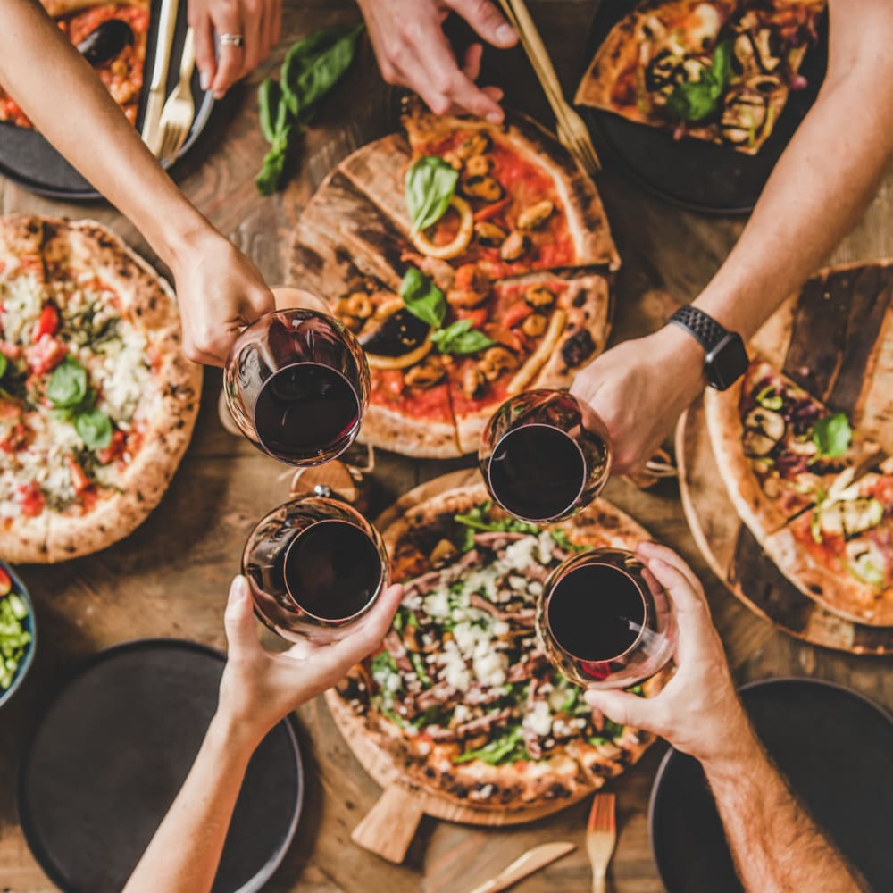 Friends enjoying wine and pizza in Newnan, Georgia near Newnan Lofts Apartment Homes
