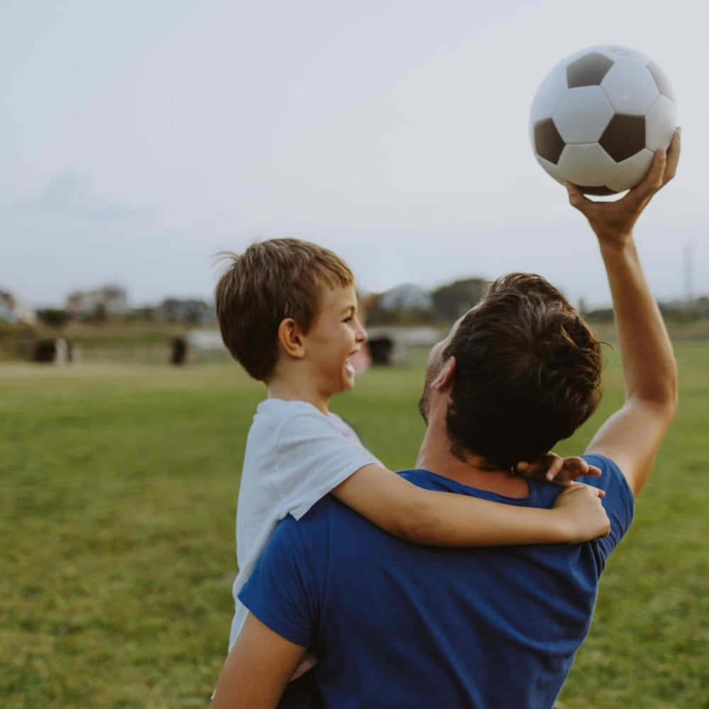 Dad playing soccer with his son at the park at Legacy Management in Ft. Wright, Kentucky