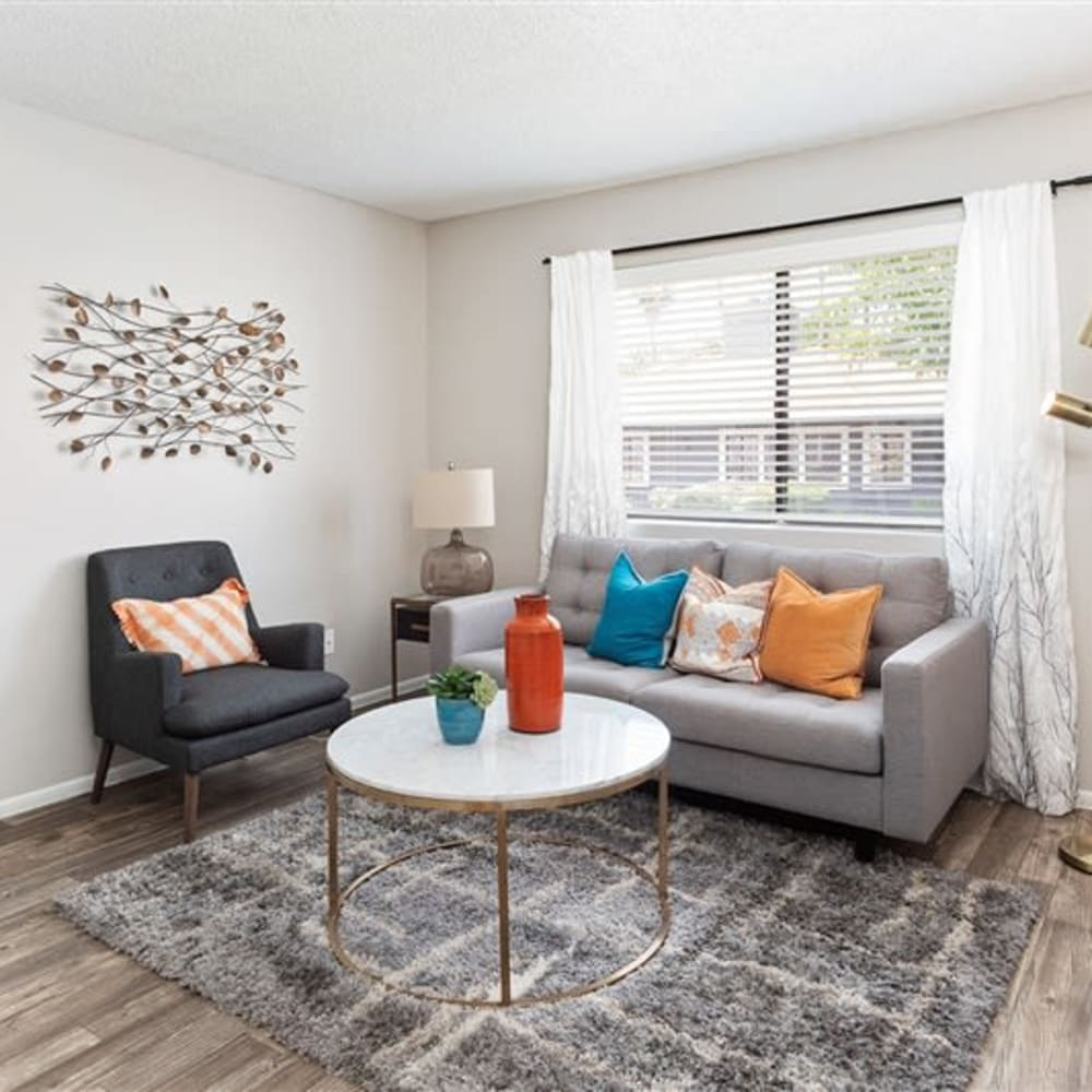 A living room with a large window at Argenta Apartments in Mesa, Arizona