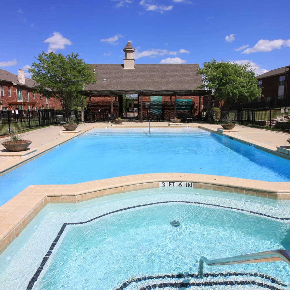 Spa next to the pool on a beautiful day at Oaks Estates of Coppell in Coppell, Texas