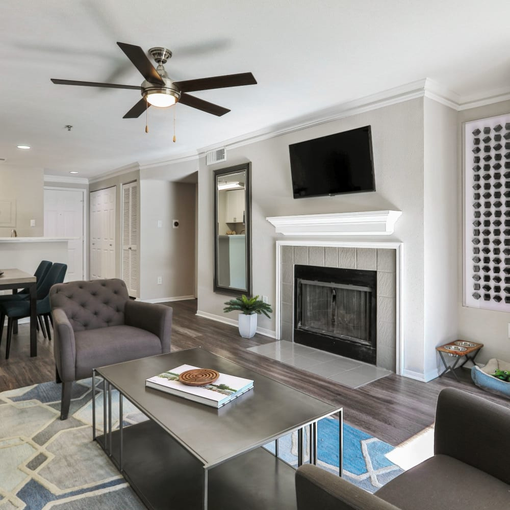 Spacious living room with tv, fireplace, and a ceiling fan at 45Eighty Dunwoody Apartment Homes in Dunwoody, Georgia