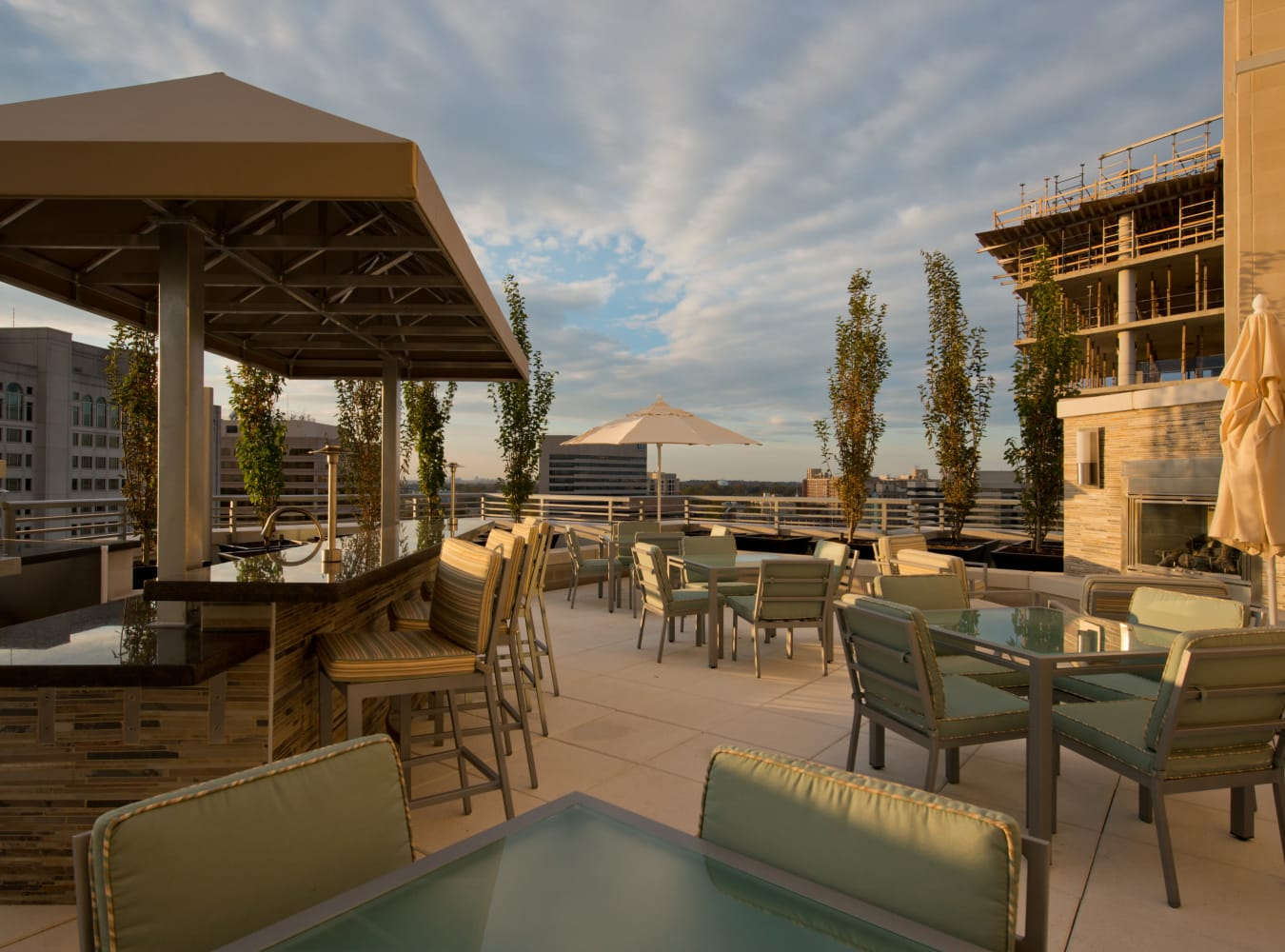 A rooftop lounge with tables and chairs for eating at Solaire 1150 Ripley in Silver Spring, Maryland