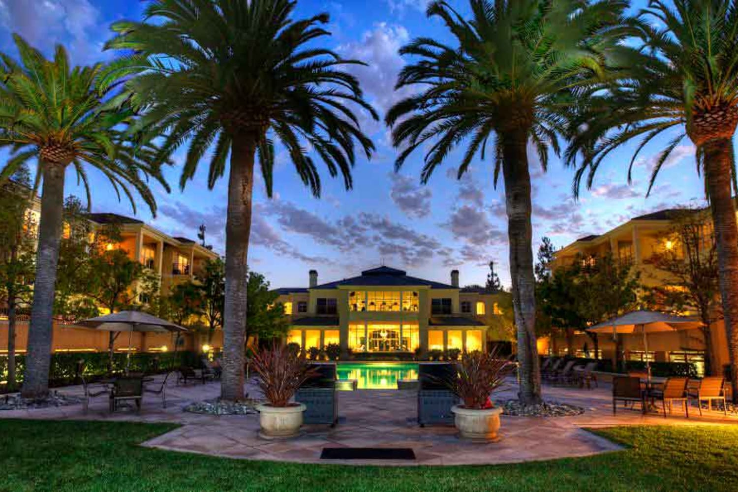 Front entrance and palm trees at dusk at The Carlyle in Santa Clara, California