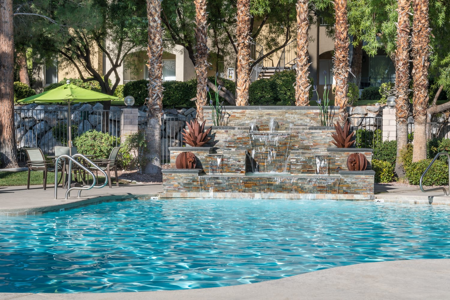 Have fun in a swimming pool with a waterfall at Rancho Destino Apartments in Las Vegas, Nevada