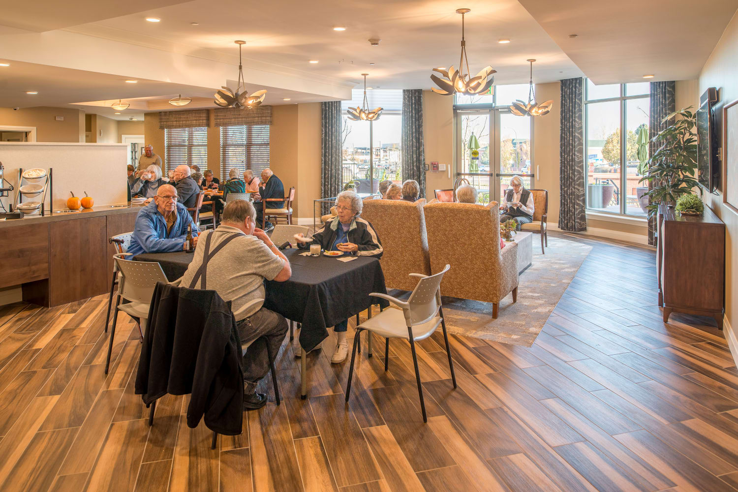 Residents in the grand dining room enjoying a meal and each others' companyat Village at Belmar