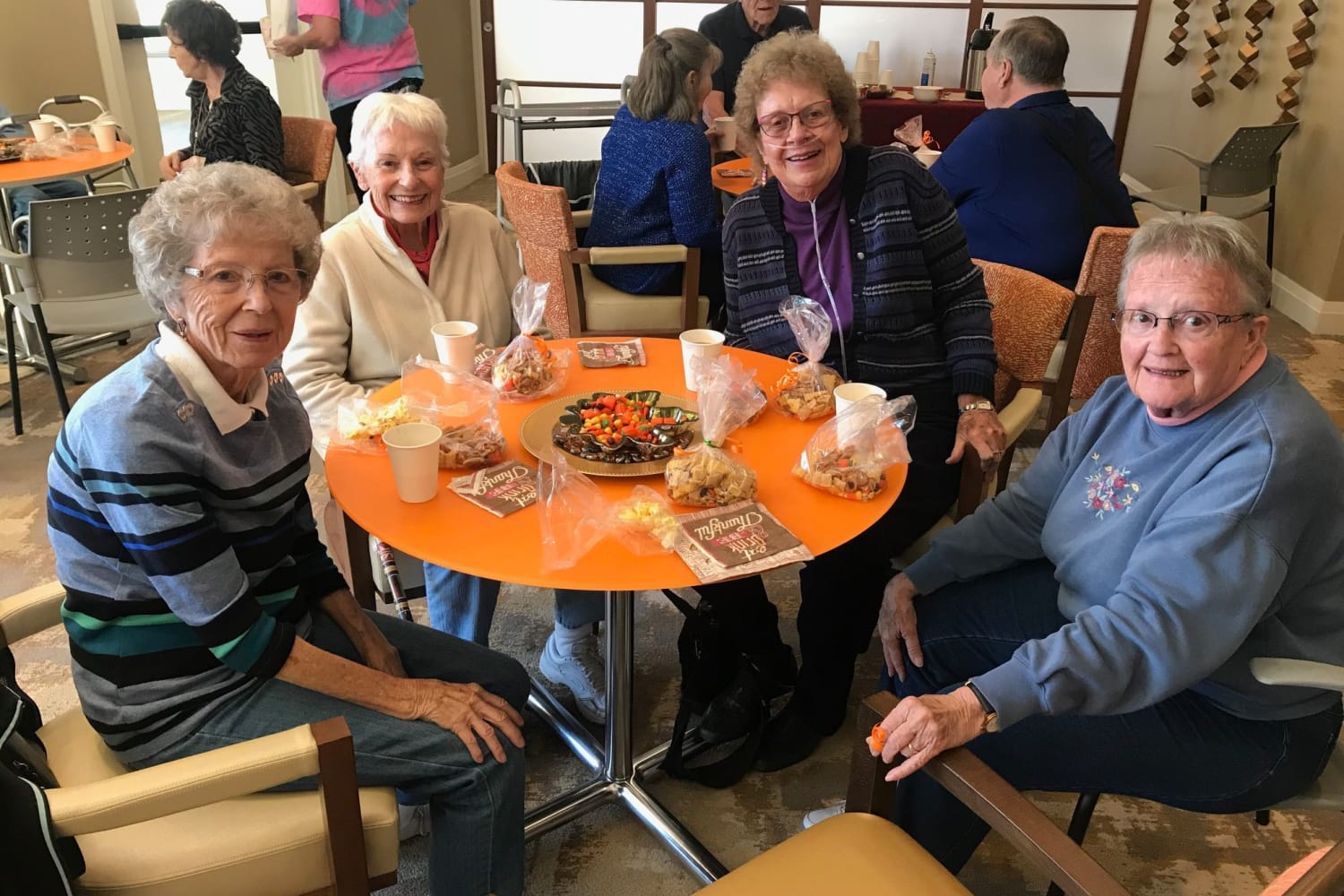 Closeup view of residents enjoying a meal together at Village at Belmar in Lakewood
