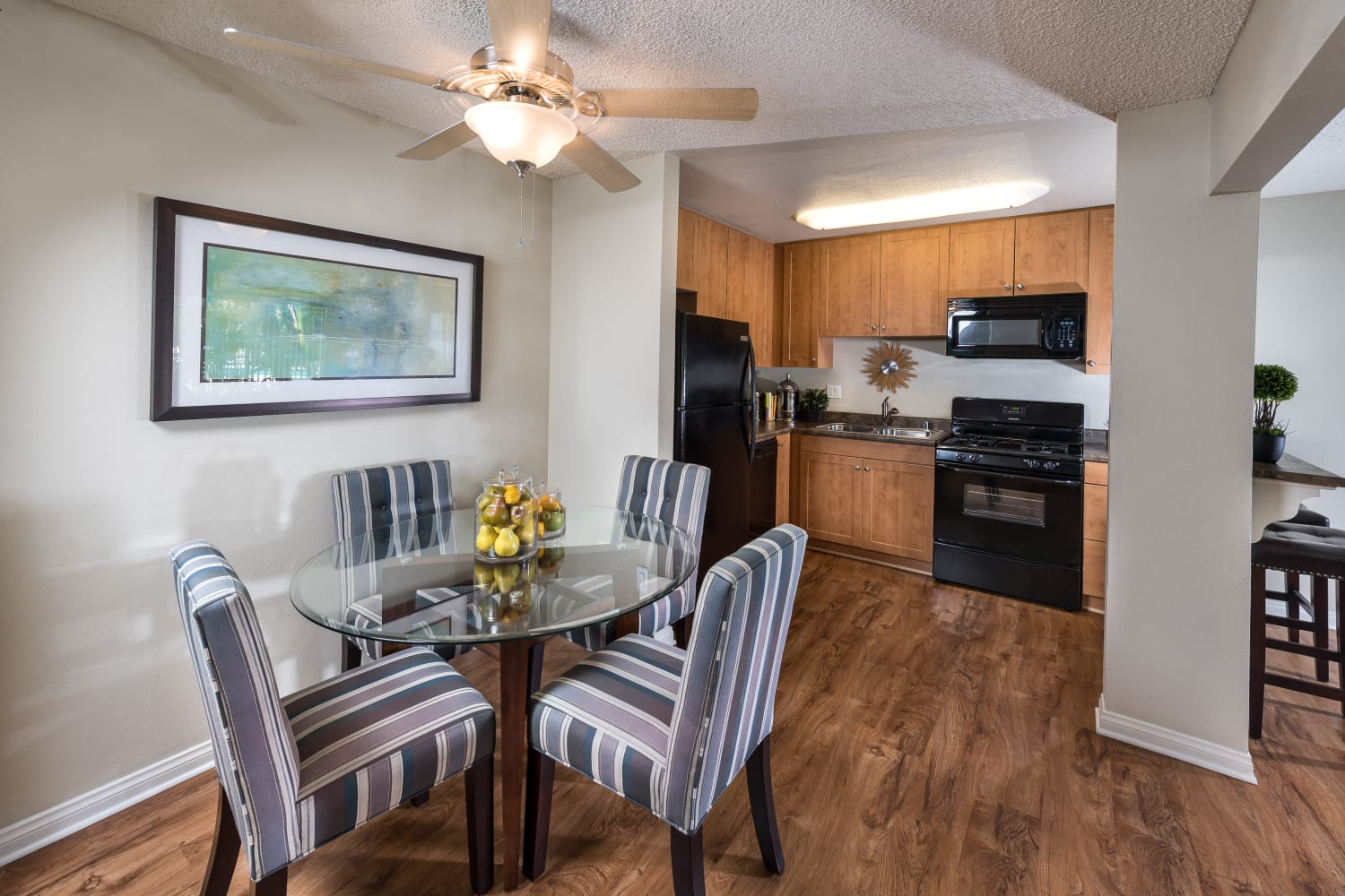 UCE Apartment Homes in Fullerton, California, offers open dining room floor plans with hardwood floors and ceiling fans