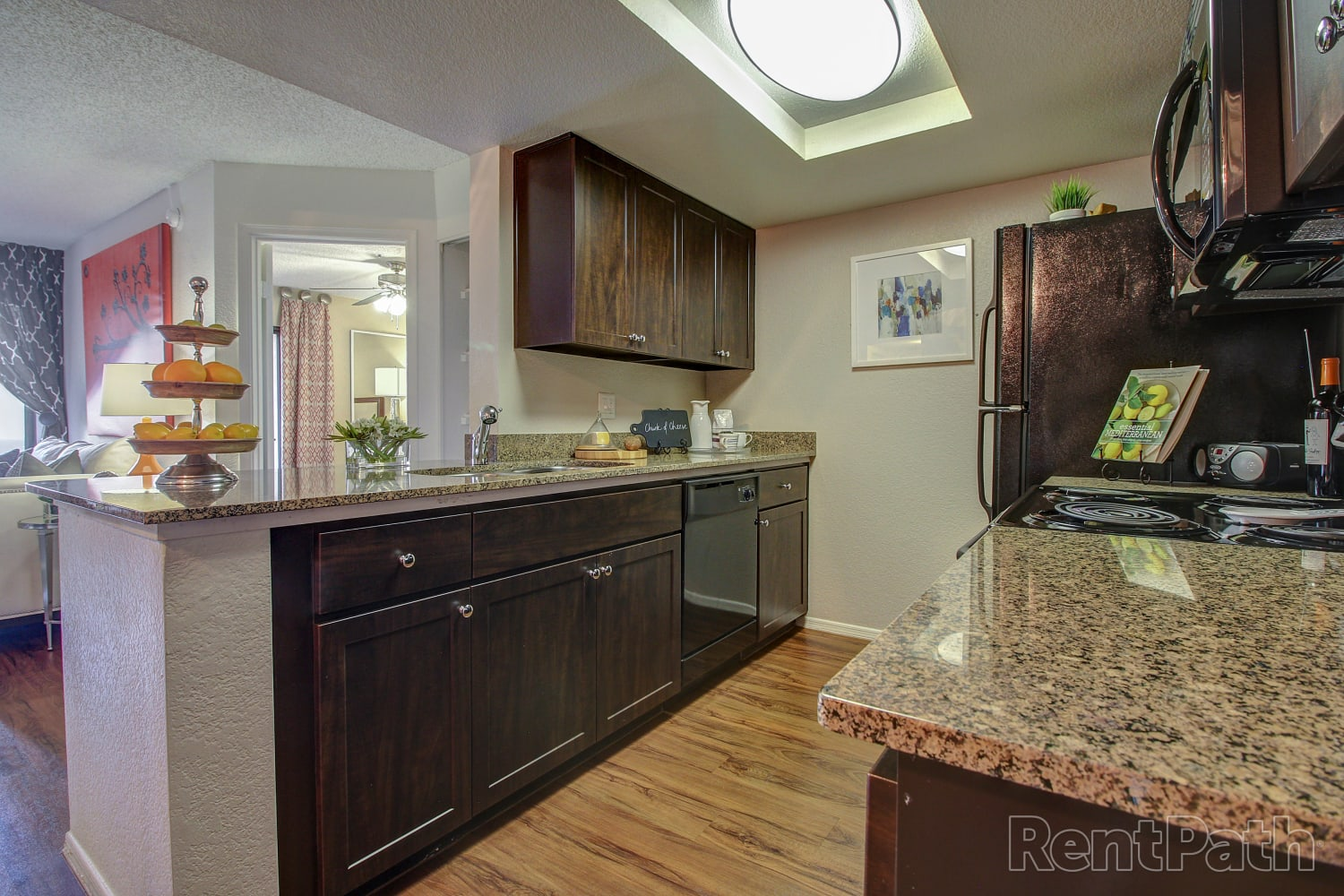 Kitchen with granite counter tops and hardwood floors at Casa Santa Fe Apartments in Scottsdale, Arizona