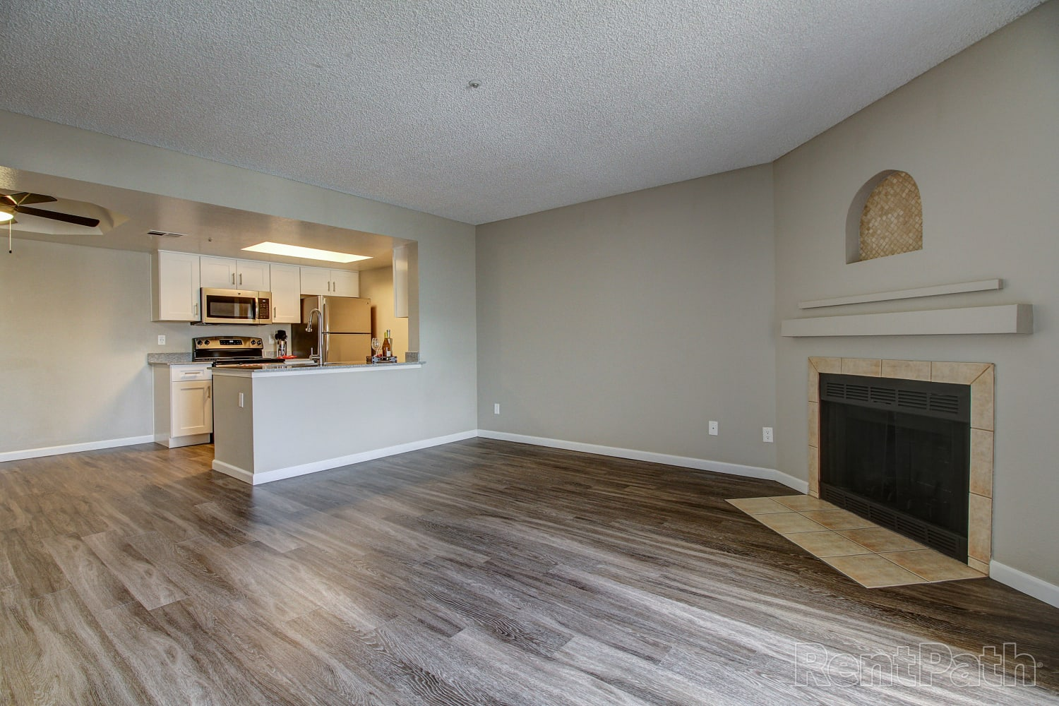 Spacious living room with a fireplace and hardwood floors at Casa Santa Fe Apartments in Scottsdale, Arizona