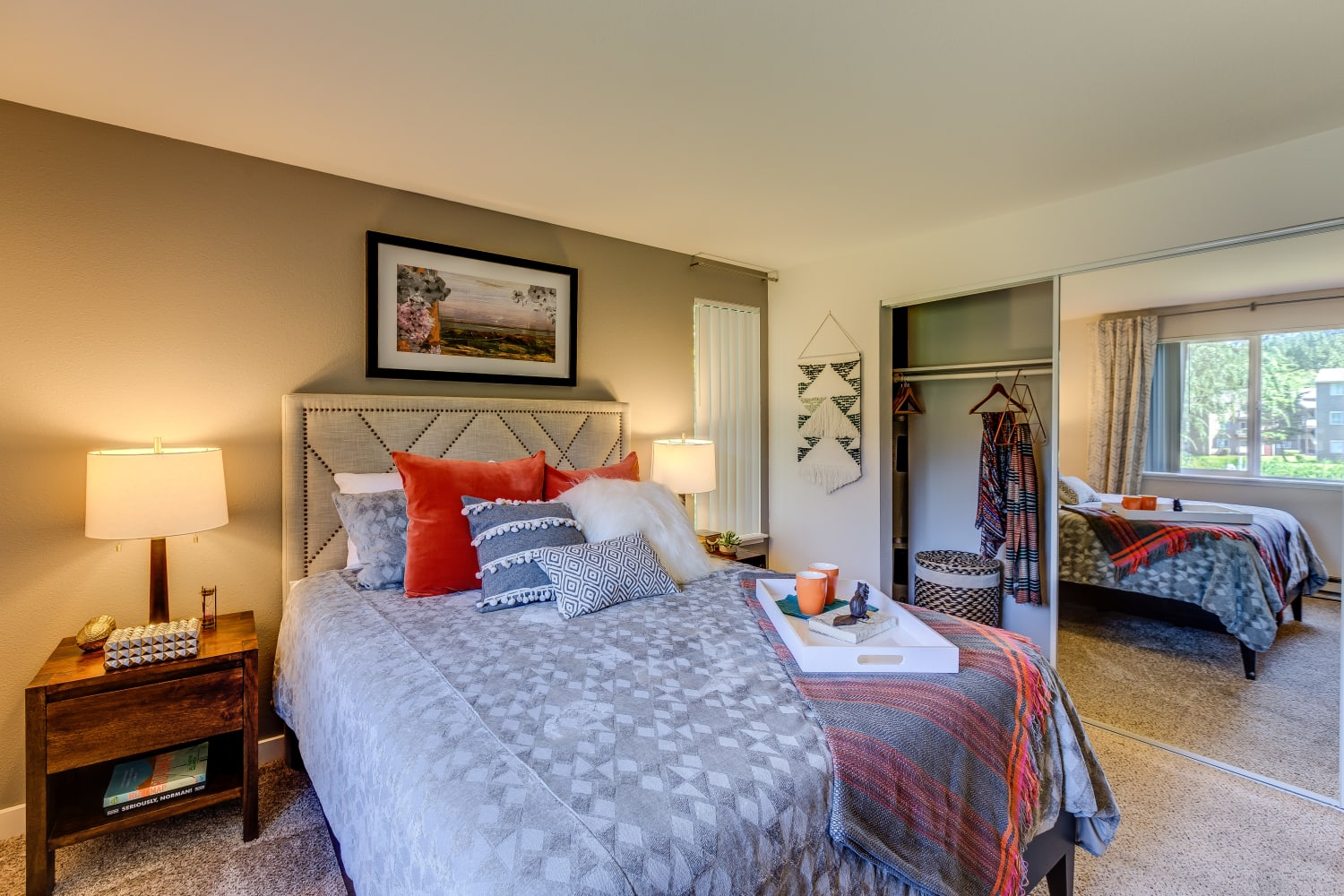 A bedroom with a mirrored cabinet door and large window at The Preserve at Forbes Creek in Kirkland, Washington