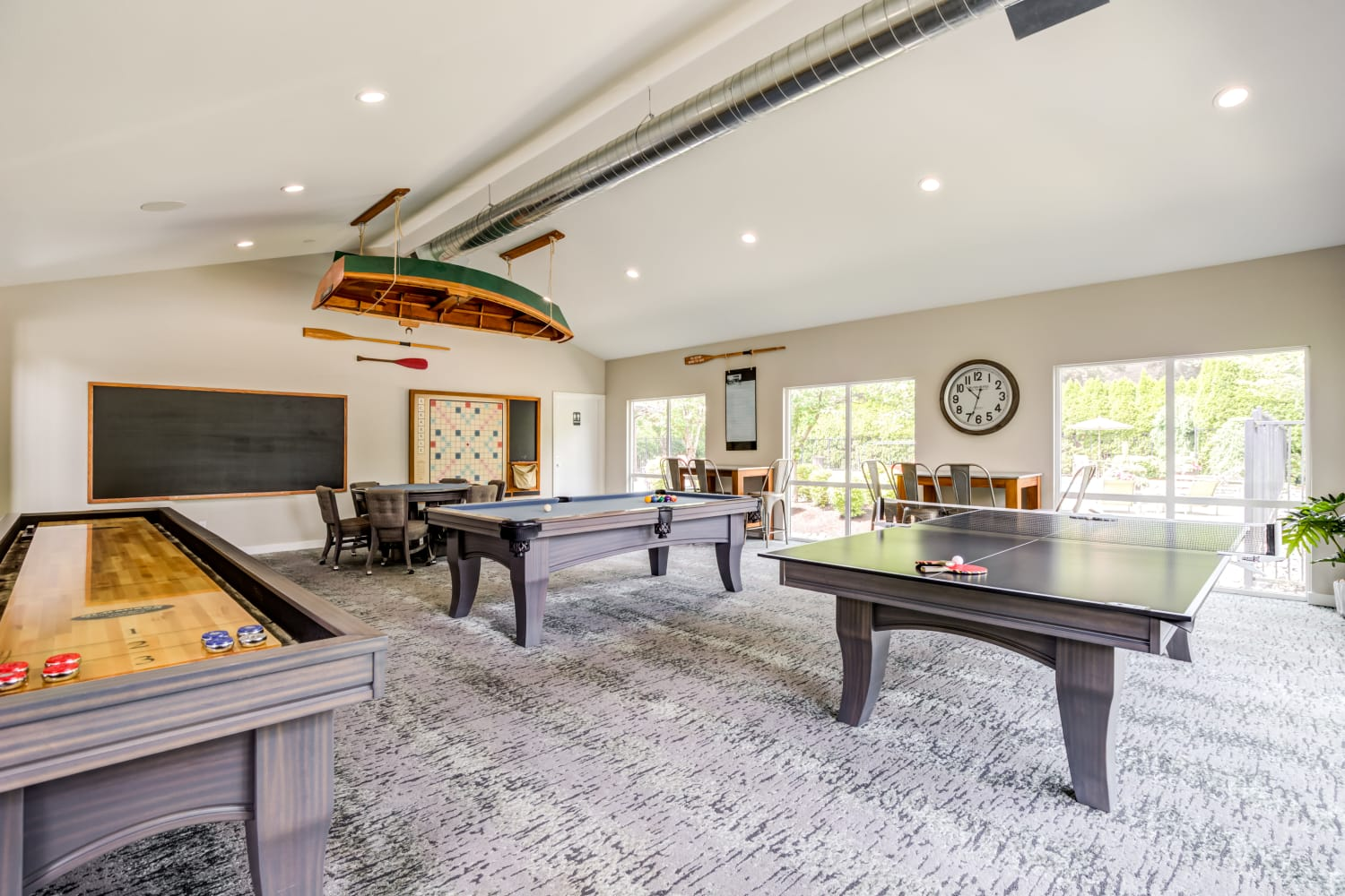 Clubhouse interior featuring a shuffleboard table and billiards table at Campbell Run Apartments in Woodinville, Washington