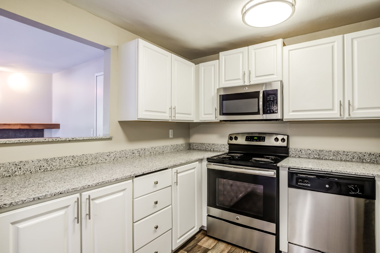 Modern Kitchen with stainless steel appliances and ample countertop space at Campbell Run Apartments in Woodinville, Washington