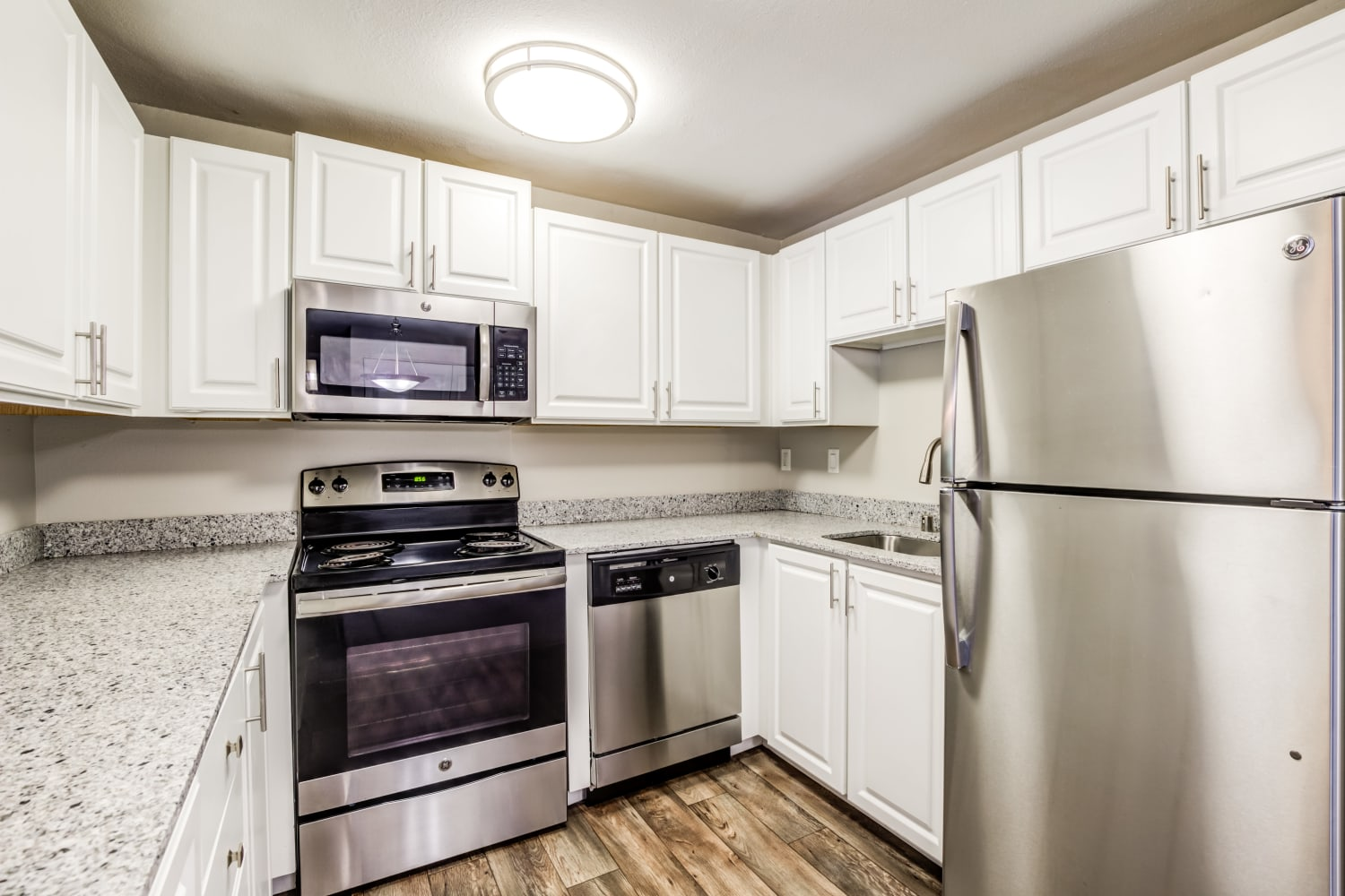 Light and bright colored kitchen featuring stainless steel appliances at Campbell Run Apartments in Woodinville, Washington