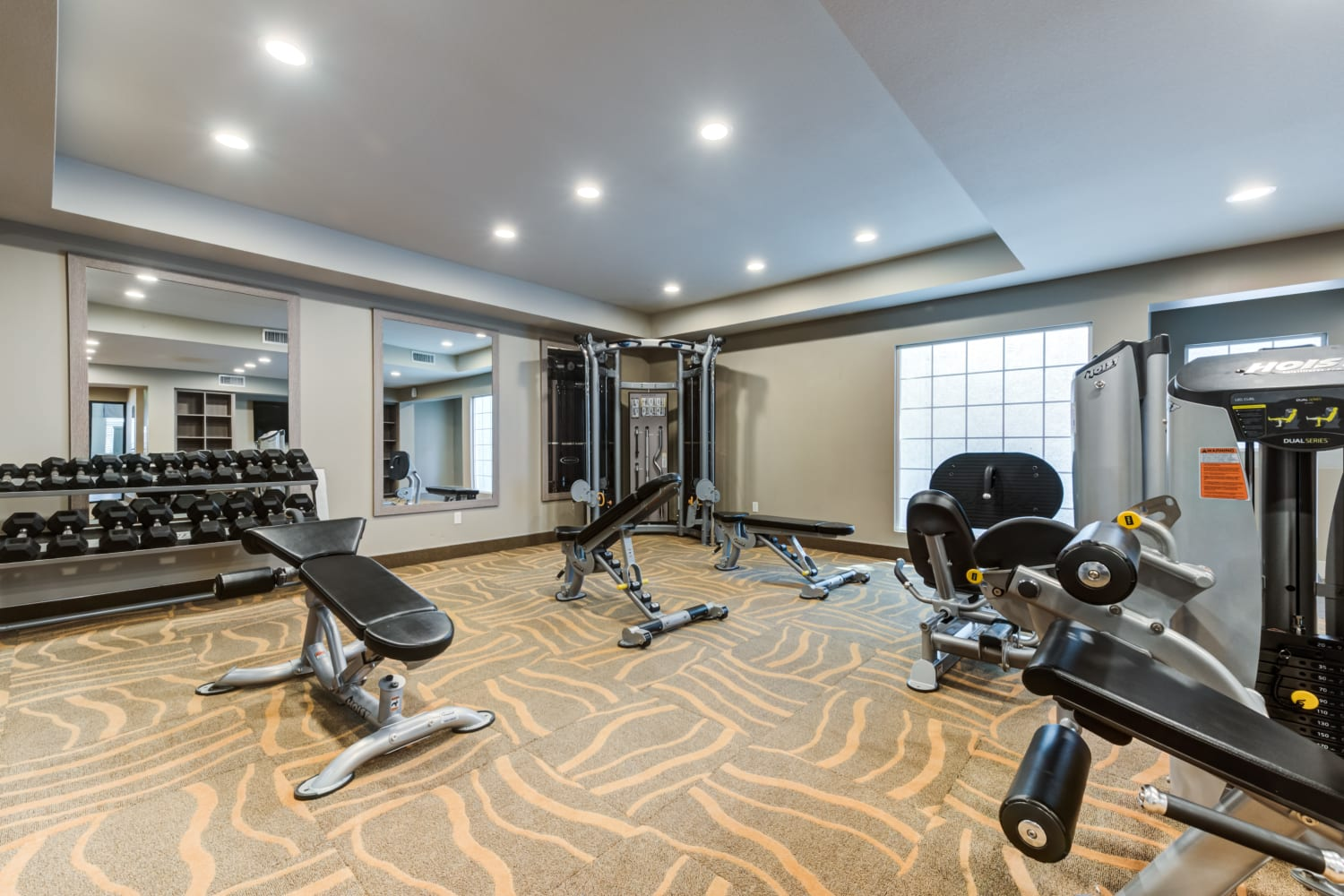 Exercise equipment and free weights in the fitness center at Sierra Heights Apartments in Rancho Cucamonga, CA