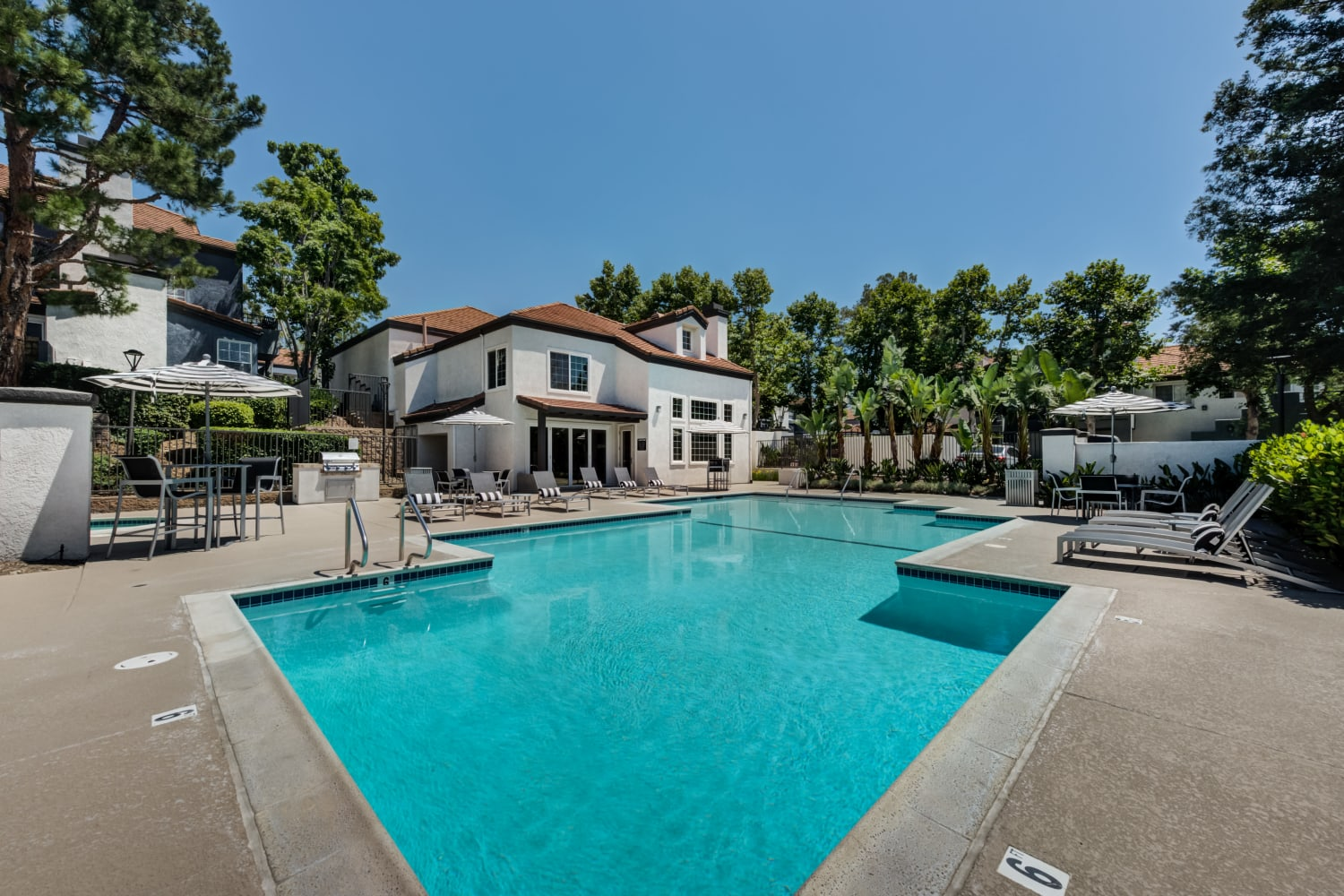 Outdoor swimming pool with clubhouse in the background at Sierra Heights Apartments in Rancho Cucamonga, CA