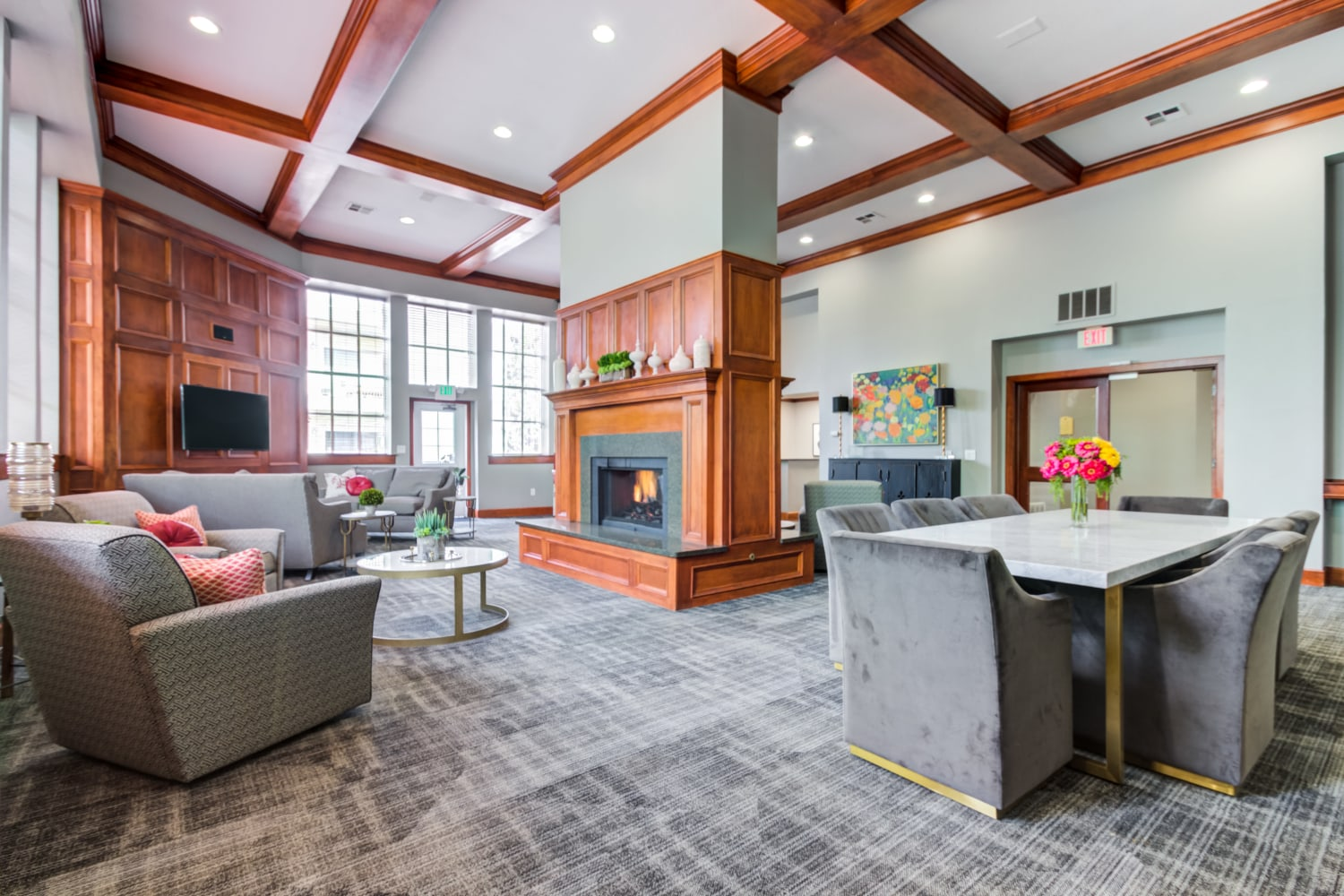 Beautiful high ceiling clubhouse interior featuring a fireplace and sitting area at Irving Schoolhouse Apartments in Salt Lake City, Utah