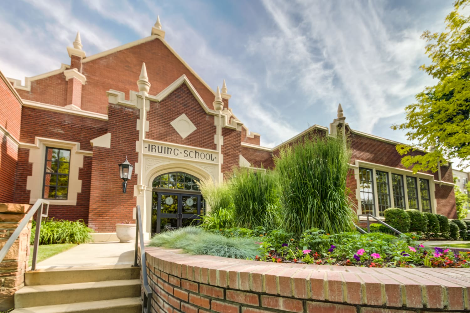 Exterior of building with landscaped garden at Irving Schoolhouse Apartments in Salt Lake City, Utah