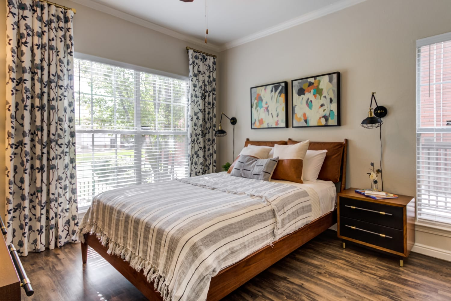 A bedroom with large windows features ample natural light and hardwood floors in an apartment at Irving Schoolhouse Apartments in Salt Lake City, Utah