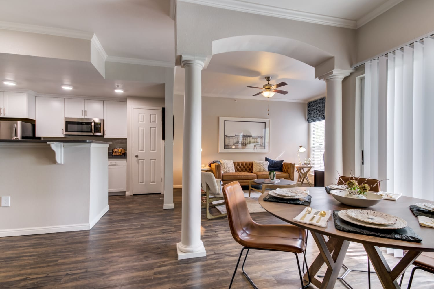 Dining table with view towards living room and kitchen featuring white cabinets and breakfast bar seating in an apartment at Irving Schoolhouse Apartments in Salt Lake City, Utah