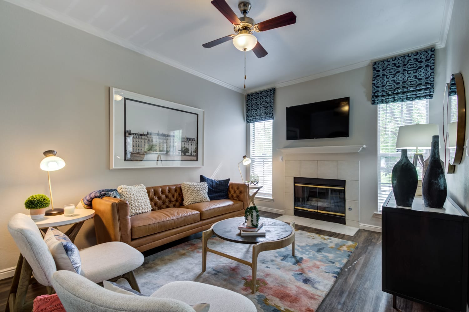Beautifully decorated living fireplace and ceiling fan at Irving Schoolhouse Apartments in Salt Lake City, Utah