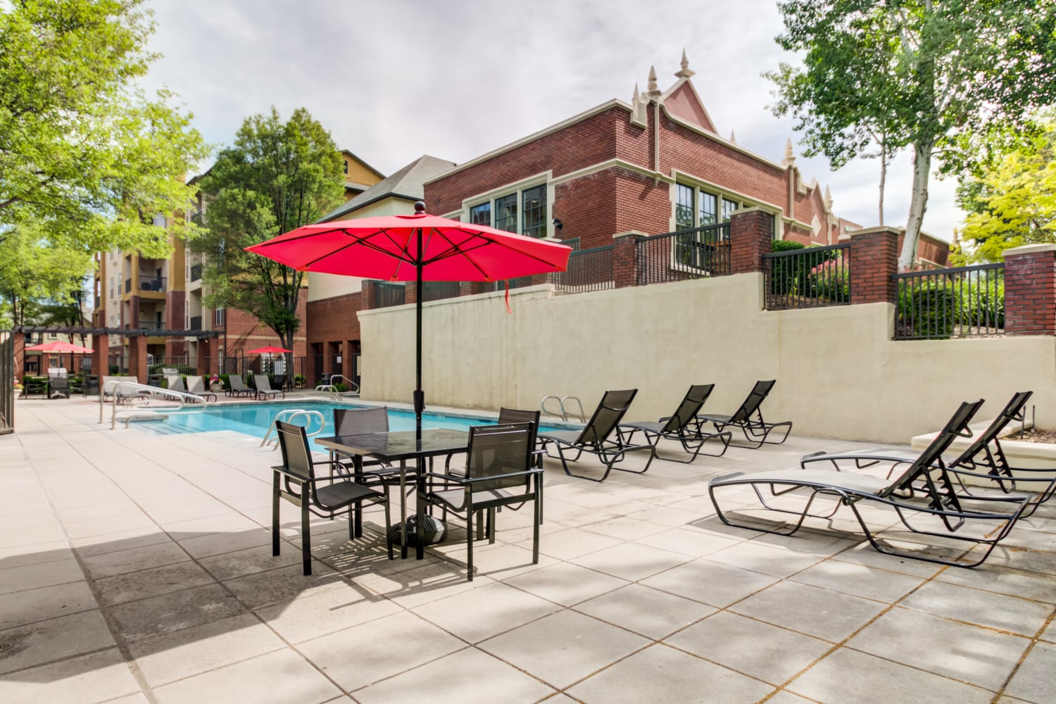 Lounge chairs and tables with umbrellas by community pool at Irving Schoolhouse Apartments in Salt Lake City, Utah