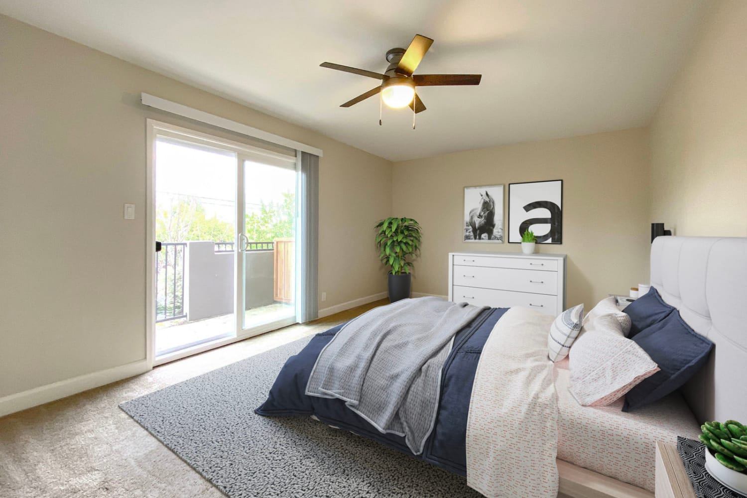 Model home's well-furnished primary suite with a sliding door to the private balcony outside at Pleasanton Heights in Pleasanton, California
